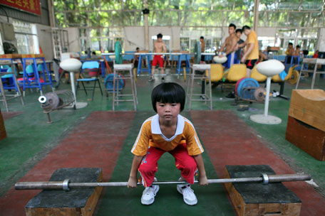 This picture taken on July 11, 2012 shows a young Chinese girl training at a weightlifting school in Xiamen, southeast China's Fujian province. Dominant China put Asia on top of the world at the Beijing Olympics but the pressure is on as they bid to repeat the feat away from home.      CHINA OUT      AFP PHOTO